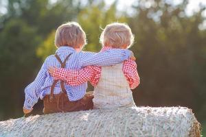 twee kleine vrienden zitten op hooibaal foto