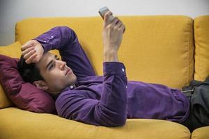 aantrekkelijke jonge man met behulp van mobiele telefoon tijdens het leggen foto