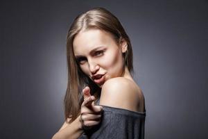 vrouw die met haar vinger beweert te schieten
