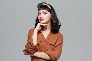 aantrekkelijke doordachte jonge vrouw in blouse met gevouwen handen foto