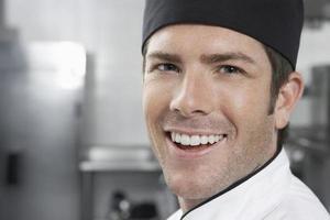 lachende mannelijke chef-kok in de keuken foto