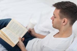 man leest een boek op zijn bed thuis foto