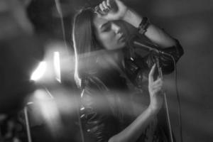 meisje zingen in een microfoon in een studio foto