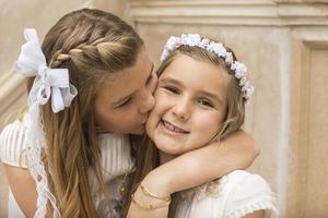 liefdevol gebaar van twee zussen bij de eerste communie foto