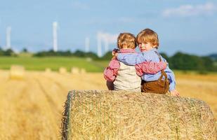 twee kleine broers en zussen jongens en vrienden zitten op hooiberg foto