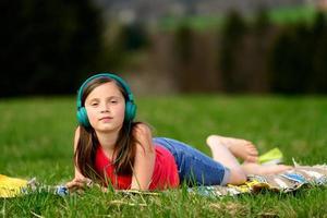 vrij jong meisje dat aan muziek in aard luistert foto