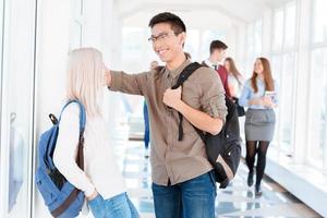 Aziatische jongen en blond meisje praten in de gang foto