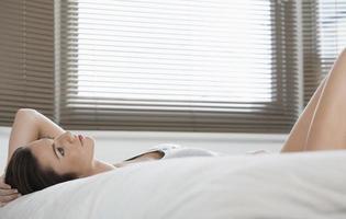 mooie vrouw dagdromen terwijl liggend in bed