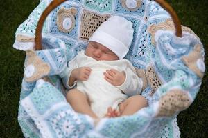 pasgeboren baby ligt op de blauwe kaft in de mand foto