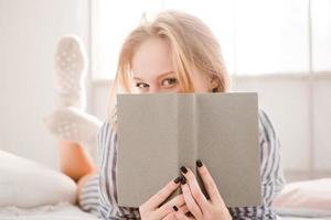 flirterige verlegen jonge vrouw bedekte haar gezicht met het boek foto