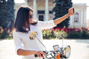 vrouw op scooter selfie foto maken