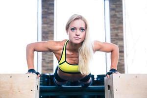 mooie sportvrouw die opdrukoefeningen op geschikte doos doet foto