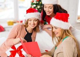 vrouwen in santa helper hoeden met kaart en geschenken foto