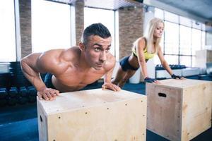 vrouw en man doen push-ups op sportschool foto