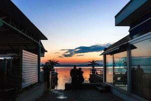 koppel kijkt romantisch zonsondergang op het meer