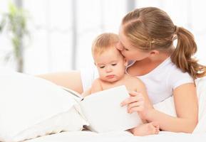 moeder leesboek baby in bed voor het slapen gaan foto