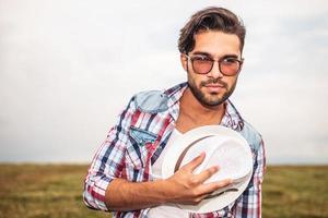 glimlachende toevallige mens die zijn hoed tegen borst houdt
