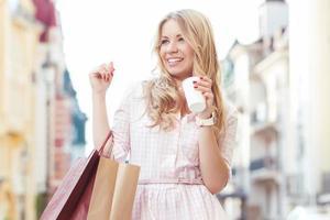 blond meisje met plezier na het winkelen foto