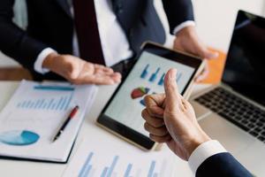 zakenlieden zitten samen aan een bureau bespreken financiële markt