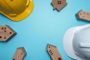 hardhats met houten huizen op blauwe achtergrond foto