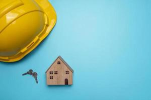 veiligheidshelm met houten huis en sleutels op blauwe achtergrond, foto