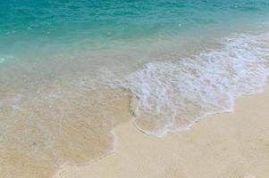 blauwe golven spatten op wit strand foto