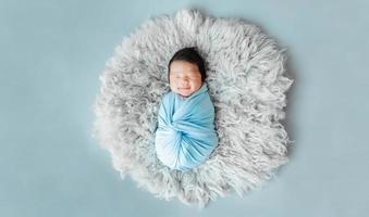 Aziatische pasgeboren baby slapen op bont foto