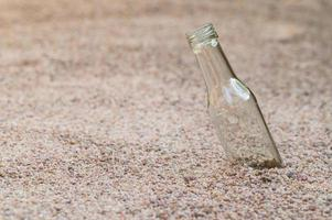 lege glazen fles op het strand foto