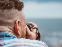 man houdt camera richting zee