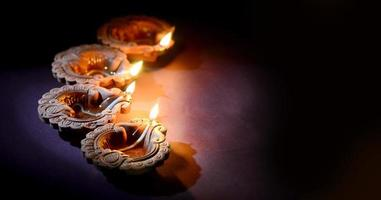 verlichte diya-lampen in een donkere kamer foto