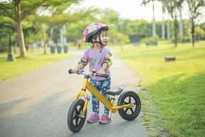 klein meisje leert fiets buiten op het fietspad foto