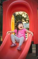 klein meisje glijdt naar beneden rode speeltuin glijbaan foto