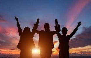 drie mensen aftekenen voor zonsondergang foto