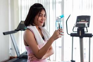 vrouw met fles water in de sportschool foto