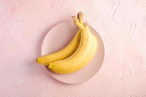 bananen op roze gestructureerde achtergrond foto