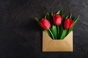 rode bloemen in een papieren envelop op gestructureerde donkere zwarte achtergrond foto