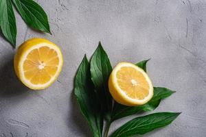twee schijfjes citroen met groene bladeren op grijze betonnen achtergrond foto