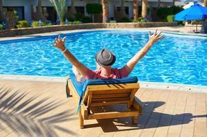 jonge man tot op een ligstoel in het hotel foto