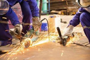 werknemers snijden metalen plaat met elektrische slijpmachine