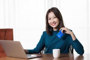 Aziatische vrouw die online winkelt foto