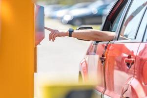 bestuurder betaalt parkeermeter foto