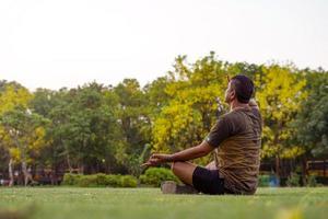 man doet yoga buiten foto