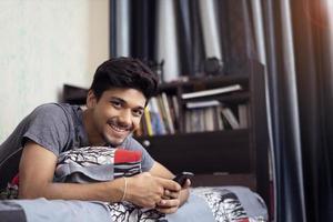 jonge Indiase jongen met behulp van zijn telefoon liggend op zijn bed foto