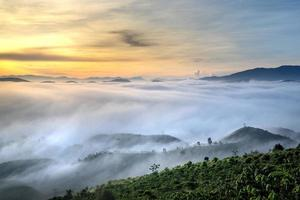 bewolkte mistige heuvels en zonsondergang foto