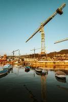 boten in water naast bouwkranen foto