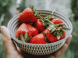 close-up van de hand met kom aardbeien foto