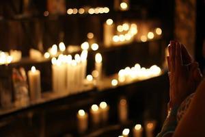 persoon bidt voor kaarsen foto