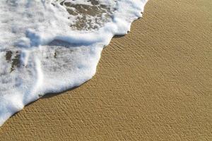 kust schuim op het strand in de zon