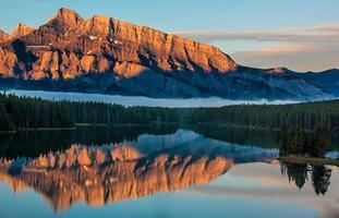 bergen door waterlichaam bij zonsondergang foto