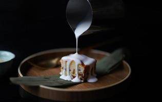 glazuur wordt gegoten op plakje cake foto